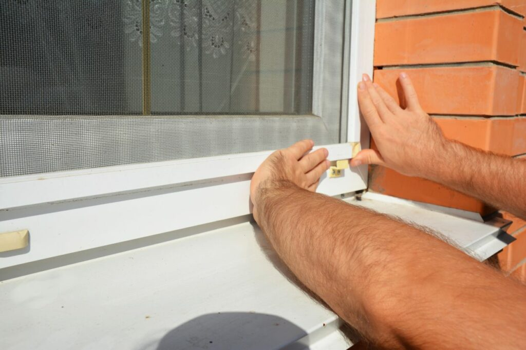 Contractor installing mosquito wire screen on house window