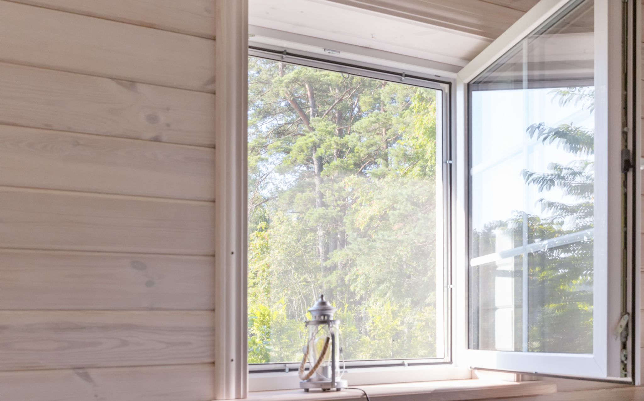 window open showing trees outside and small lantern on window sill